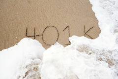 401k in the sand. 401k written in the sand with an ocean wave washing it away royalty free stock images