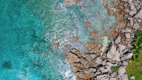 4k satellietbeeld verticale videogolven die op rotsachtige granietrotsen aankomen van het eiland van La Digue Glashelder water me