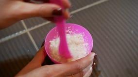 4K schoonheidsconcept De handen van vrouwen bewegen alginate gezichtsmasker in een roze kopclose-up stock videobeelden