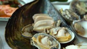 4K schotel van vers tweekleppige schelpdieren Zuidkoreaans Restaurant in Jagalchi-Vissenmarkt Busan stock footage