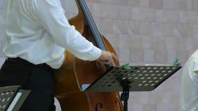 4k se cierran para arriba de un hombre que juega en el violoncelo en la etapa almacen de metraje de vídeo