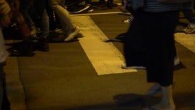 4K se cierran para arriba en la muchedumbre que los peatones caminan a través de tiempo de la precipitación del camino en la igua almacen de metraje de vídeo