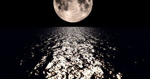 A 4K sepia colored moon setting slowly over the ocean at night with the color of the moon reflecting light onto the ocean waves stock video