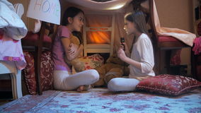 4k shot of girl telling story to her friend in tepee tent at night stock video footage