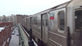 4k shot of huge modern urban silver steel subway car train arriving at metro tube station busy Brooklyn downtown street stock footage