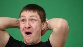 4K si chiudono su di un uomo emozionale sorpreso che esamina la macchina fotografica su fondo verde archivi video