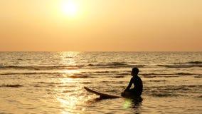 4K silhouette d'homme de surfer se reposant sur la planche de surf au-dessus de la mer au coucher du soleil sur la plage tropical banque de vidéos