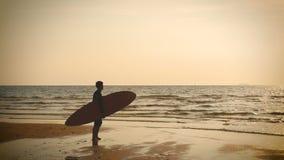 4K silhouette de support d'homme de surfer sur la plage de mer avec de longs panneaux de ressac au coucher du soleil sur la plage banque de vidéos