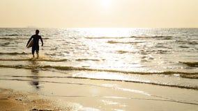 4K Silhouette du jeune homme heureux de ressac courant avec de longs panneaux de ressac au coucher du soleil sur la plage tropica banque de vidéos
