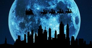 A 4K silhouette of Santa Claus and his reindeers flying over the city skyline at night with a gigantic blue winter moon in the bac stock video