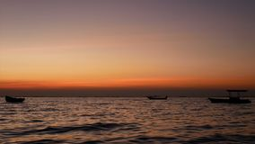 4K. silhouette of small boat over the sea with small wave at sunset or sunrise time, beautiful sunlight reflect with water surface.  stock footage