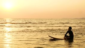 4K. silhouette of surfer man relax by sitting on surfboard over the sea at sunset on tropical beach. sport and recreation