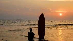 4K. silhouette of surfer man sitting on the sea beach with long surf boards at sunset on tropical beach.  stock footage