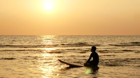 4K. silhouette of surfer man sitting on surfboard over the sea at sunset on tropical beach stock footage