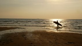 4K. Silhouette of surfer man walking into the sea with long surf boards at sunset on tropical beach.  stock video footage