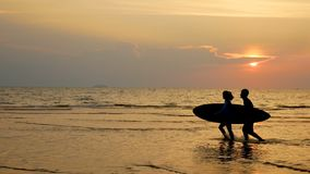 4K. silhouette of young happy surf man and woman running with long surf boards at sunset on tropical beach. surfer on the beach. In sea shore at sunset time stock video