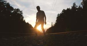 4k - A silhueta de um jovem dançando krump perto da trilha de trem contra o sol, em câmera lenta video estoque