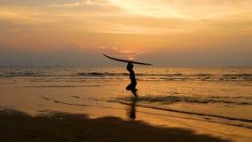 4K Silhueta do homem feliz novo da ressaca que corre com placas de ressaca longas no por do sol na praia tropical surfista na pra video estoque