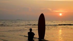 4K silhueta do homem do surfista que senta-se na praia do mar com placas de ressaca longas no por do sol na praia tropical filme