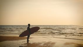 4K siluetta del supporto dell'uomo del surfista sulla spiaggia del mare con i bordi di spuma lunghi al tramonto sulla spiaggia tr stock footage