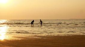 4K siluetta di funzionamento del fratello e della sorella e di gioco in acqua alla spiaggia sul tramonto bellezza ed amici allegr stock footage