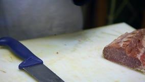 4K slaktare shoppar in brämgrisköttfransyskan, genom att använda kniven för att klippa kött i en livsmedelsbutik lager videofilmer