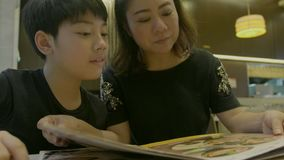 4K Slow motion of Asian cute boy with mother reading menu book and point .Happy face stock footage
