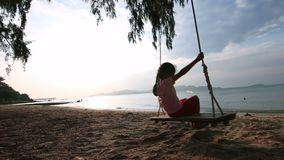 4K Slow motion Asian little girl playing swing on the beach with evening ambient light.  stock video