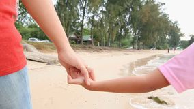 4K Slow motion mother and daughter walking hand in hand on the beach.  stock video