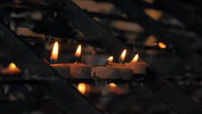 Close-up shot of many burning candles in the catholic church with the dark blured background stock video