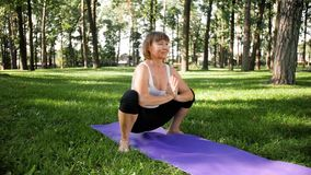 4k slow motion video of 40s woman practicing yoga on grass at park. Adult lady doing fitness exercises on mat at forest. 4k slow motion footage of 40s woman stock video footage