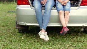 4k sluit omhoog geschoten van voeten van een vrouw en een kindzitting in de boomstam stock videobeelden