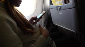 4k, smartphone asiático de la tenencia de la mujer embarazada y tacto de su panza en el avión almacen de video