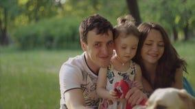 4K som den lyckliga unga familjen sitter in, parkerar Stående stock video