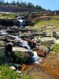 4k som förbluffar Rocky Mountain den höga glaciären, strömmar vattenfallet i sommaren Arkivbilder