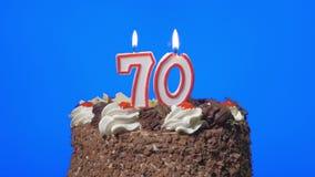 4k - Soufflant le numéro soixante-dix bougies d'anniversaire sur un gâteau de chocolat délicieux, écran bleu banque de vidéos