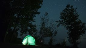 Starry sky timelapse. 5K Starry sky timelapse with tent on the coast of a river. Flicking tent stock footage