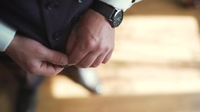 4k Stylish man in a suit fastening buttons on his jacket preparing to go out. Stylish man in a suit fastening buttons on his jacket preparing to go out. Close up stock footage