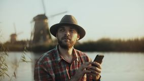 4K Successful Caucasian man sits near sunset lake. Farming businessman in a hat using smartphone app. Mobile office. stock video footage