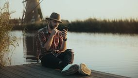 4K Successful European farmer sits on a lake pier. Man in checked shirt and hat using smartphone. Mobile shopping app. stock video