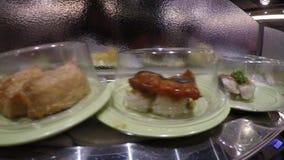 4k, sushi na correia transportadora no restaurante de Japão, igualmente conhecido como o trem do sushi video estoque
