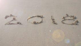4K 2018 szczęśliwy nowy rok rok 2017 pisze na piaskowatej plaży, falowa pluśnięcie zmiana rok 2018 z dźwiękiem ocean fala odlicza zbiory wideo