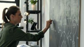 4K Teacher writing math formulas on blackboard and talking to her class 20s 4k.  stock video footage