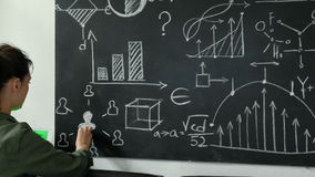 4K Teacher writing math formulas on blackboard and talking to her class 20s 4k. 4K Teacher writing math formulas on blackboard and talking to her class 20s 4k stock footage