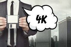 4K text on speech bubble with businessman. Holding diskette Royalty Free Stock Image