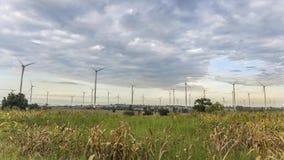 4K tijd-overlappingen windturbines het draaien Windmolen met de voorgrond van het graangebied en de achtergrond van de wolkenheme stock videobeelden