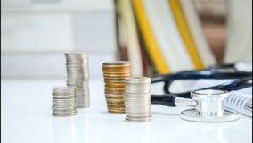 4K tijdtijdspanne van Geldmuntstukken gestapelde daling met stethoscoop stock videobeelden
