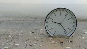 4K time concept background, big white clock in sand beach sea. 4K time concept background, big white wall clock w black arrows on sand beach sea ocean and sea stock video footage