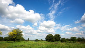4K. Time lapse clouds over the green field. stock video footage