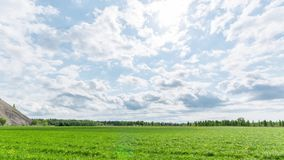 Hyperlapse footage of beautiful clouds above the green field. stock video footage